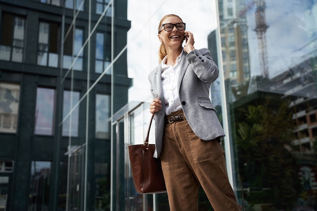 안경을 쓰고 휴대폰으로 통화하는 클래식한 옷을 입은 행복한 성공적인 비즈니스 여성