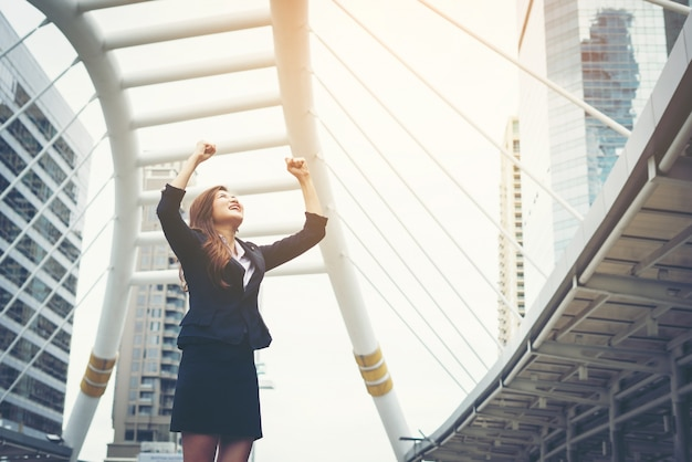 Happy success businesswoman overlooking into the city center hands raised.