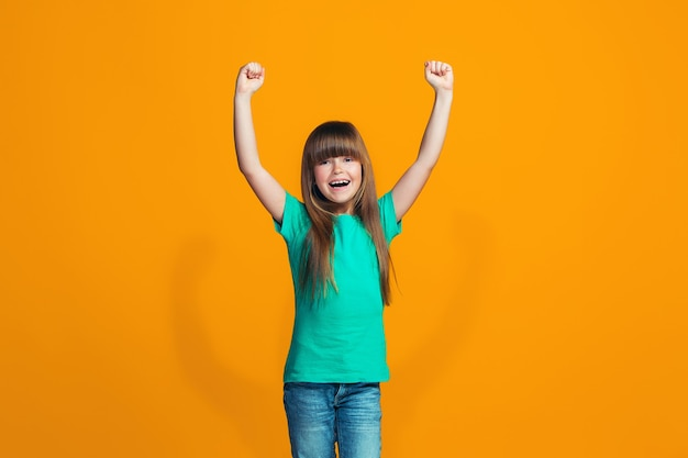 Happy success teen girl celebrating being a winner. dynamic energetic image of female model