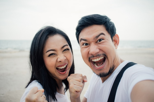 Happy and success yeah face of couple tourist on romantic beach vacation trip.