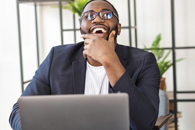 幸せに成功したアフリカ系アメリカ人の若い男性のフリーランサーまたはマネージャーがオフィスの机に座っています。成功した取引や新しいビジネスプロジェクトに喜ぶ