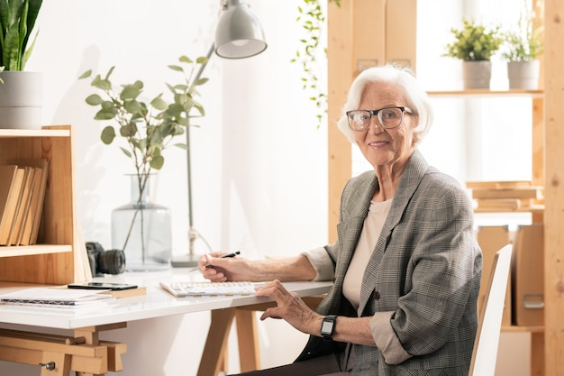Happy successful aged businesswoman in formalwear and eyeglasses sitting by desk and organizing work
