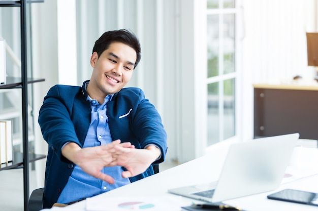 Happy of successful asian young businessman on laptop computer, tablet with blank touch screen isolated and pen on notebook on white wooden table in office