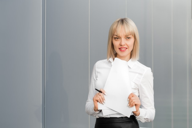 Happy successful beautiful cheerful young businesswoman or student girl standing against grey background.