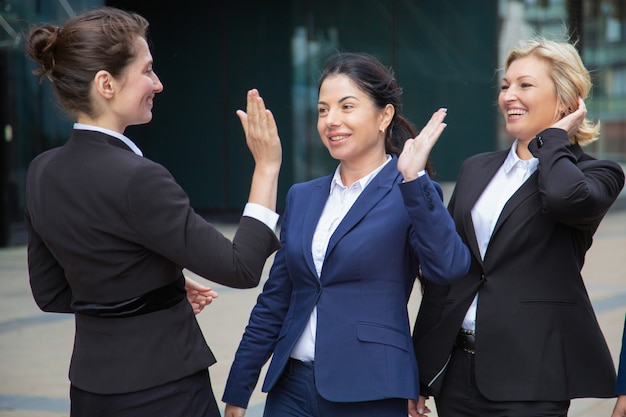 Happy successful business ladies giving high five. businesswomen wearing suits meeting in city. team success and teamwork concept