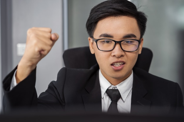 Happy successful business man using laptop computer