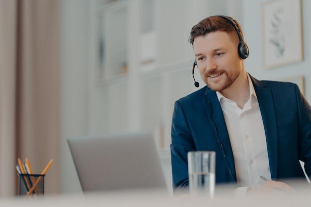 Счастливый успешный бизнес-профессионал в костюме и гарнитуре, работающий онлайн на портативном компьютере или слушающий бизнес-вебинар, сидя в гостиной дома. концепция удаленной работы