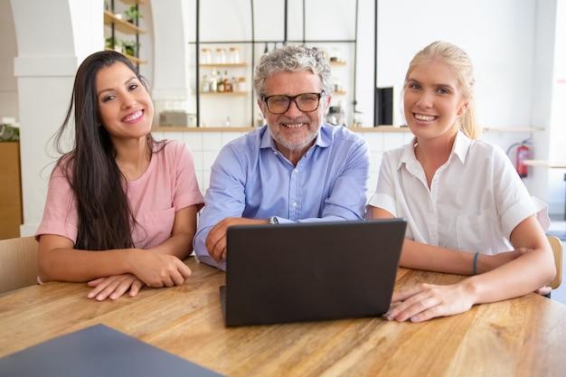 開いたラップトップでテーブルに座って、カメラを見て、ポーズと笑顔で幸せな成功したビジネスチーム