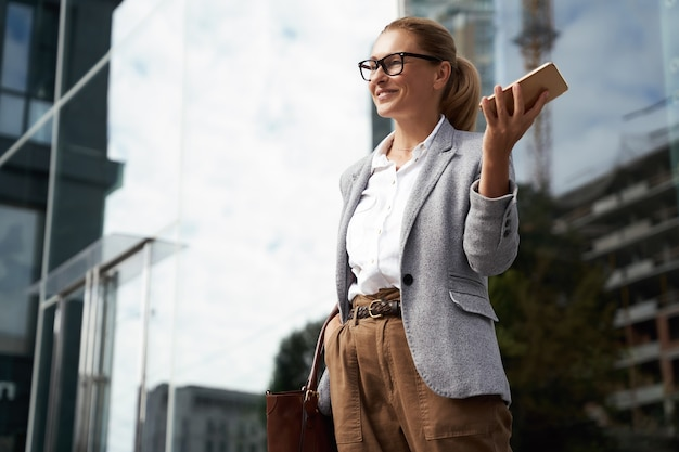 眼鏡と携帯電話を保持している古典的な服を着て幸せな成功したビジネス女性と