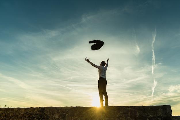 Счастливый успешный бизнесмен празднует, стоя на горизонте на стене силуэт на фоне солнца с копией пространства, подбрасывая его куртку в воздухе с распростертыми руками.