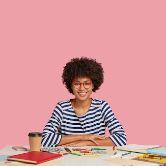 행복한 성공적인 디자이너는 선원 스웨터를 입고, 테이블에 손을 얹고, 걸작을 그리기 위해 크레용을 사용하고, 넓게 미소를 짓고, 텍스트를위한 여유 공간이있는 분홍색 벽 위에 고립 된 테이크 아웃 커피를 즐깁니다.