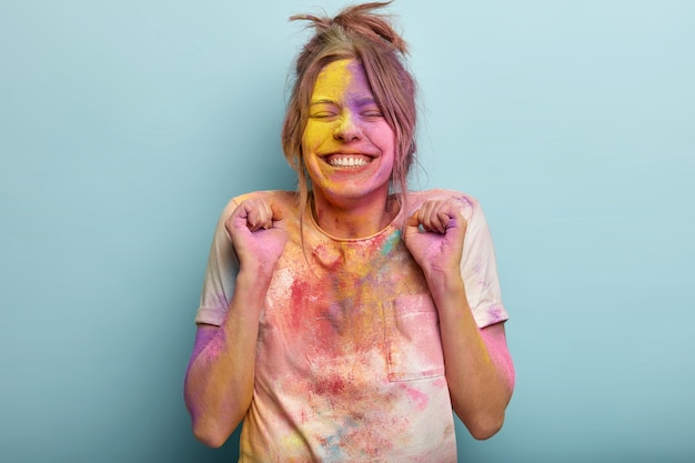 Happy successful girl clenches fists with triumph, laughs positively, celebrates holi fest, wears casual t shirt smeared with colored powder, closes eyes and shows white teeth, isolated on blue wall