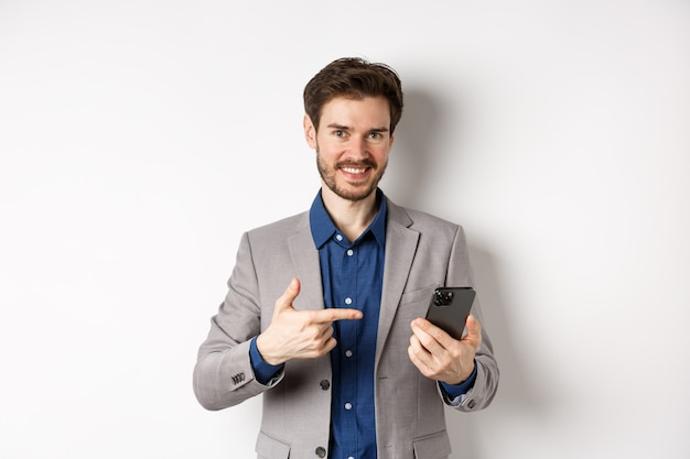 Happy successful man in suit pointing at cellphone, advertising mobile app, standing on white background.