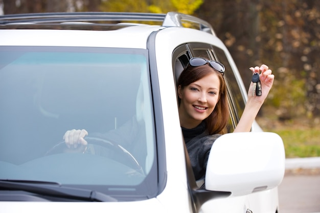 新しい車からの鍵を持つ幸せな成功した女性