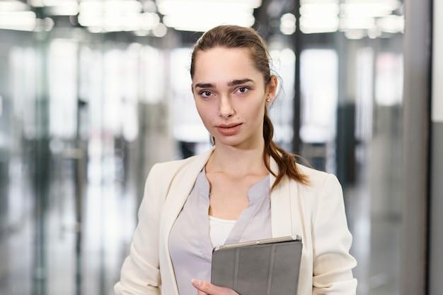 Счастливая успешная женщина с планшетом на современном коридоре офиса.