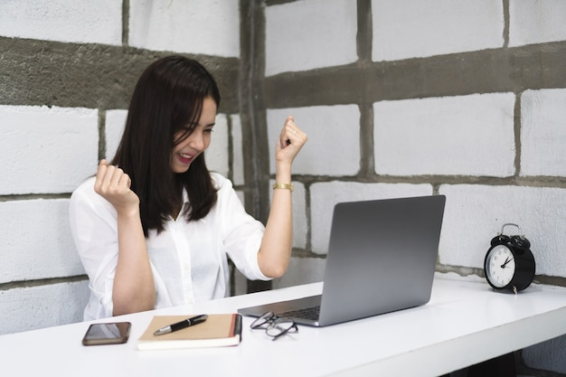 Happy successful young asian woman celebrate while working with laptop at home.