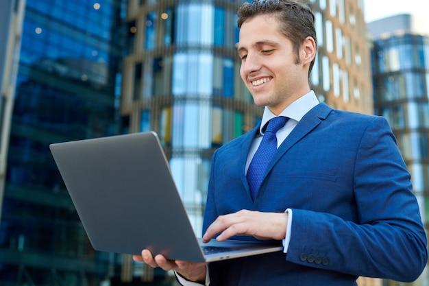 高層ビルの外で現代のラップトップに取り組んで幸せな成功した青年実業家