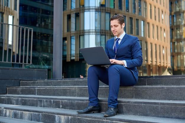 現代のラップトップで作業し、イヤホンを使用し、高層ビルの外の階段に座って幸せな成功した青年実業家