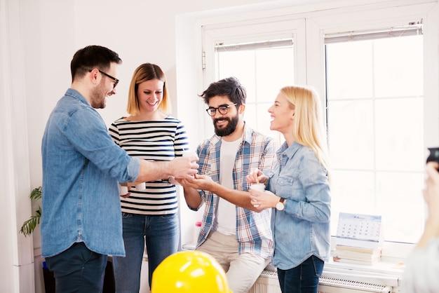 Счастливые успешные молодые дизайнеры отдыхают в своем офисе.