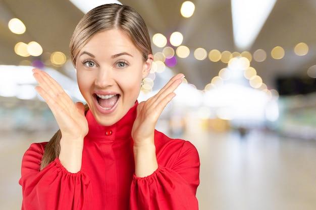 叫び、成功を祝う挙手で幸せな成功した若い女性