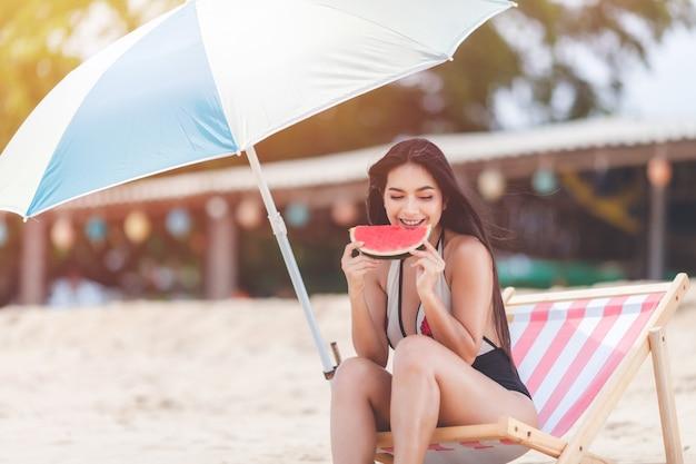 Счастливого лета и отпуска, праздника, долгих выходных на пляже. сексуальная женщина расслабляется в бикини, сидя на шезлонге и тропических фруктах арбуза, улыбается и расслабляется