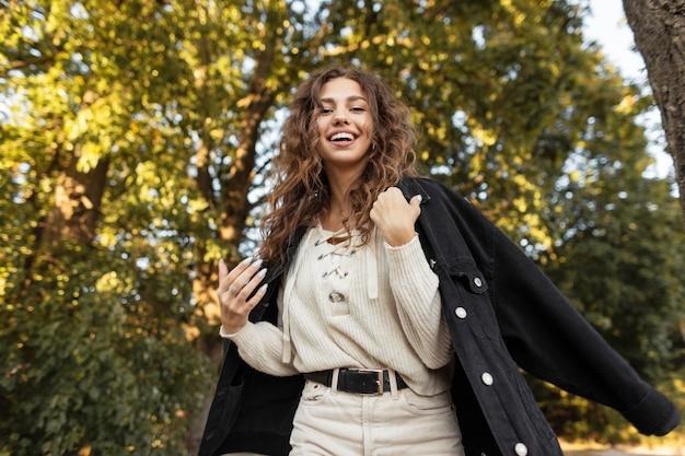 곱슬머리를 한 아름다운 젊은 여성 모델의 행복한 여름 초상화와 데님 재킷과 니트 블라우스를 입은 귀여운 미소가 자연 속에서 즐기고 걷습니다. 캐주얼한 여성의 스타일과 아름다움
