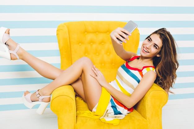 Felice ora legale di gioiosa ed elegante donna ypung in abito colorato, con lunghi capelli ricci bruna facendo selfie in sedia gialla sulla parete a strisce. divertirsi, esprimere emozioni positive.