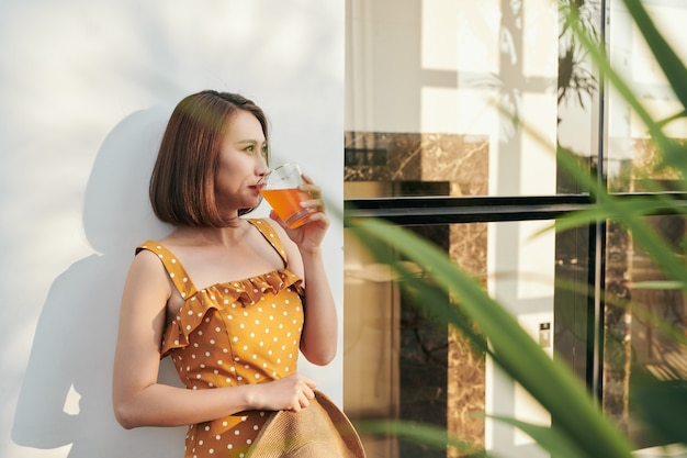 壁の後ろでオレンジ ジュースを楽しむ幸せな夏の女性