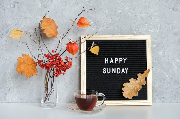 Happy sunday text on black letter board and bouquet of branches with yellow leaves on clothespins in vase and cup of tea