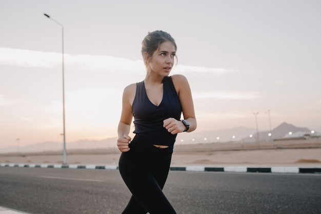 Happy sunny morning moments of hardworking motivated amazing young woman in sportswear running on road in early morning un tropical country. training, workout, healthy lifestyle