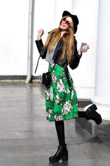 Felice tempo di primavera soleggiata di bella giovane donna con lunghi capelli castani in cappello, gonna lunga verde, sui tacchi che camminano sulla strada. modello alla moda, che esprime emozioni positive alla fotocamera, sorridente, gioia