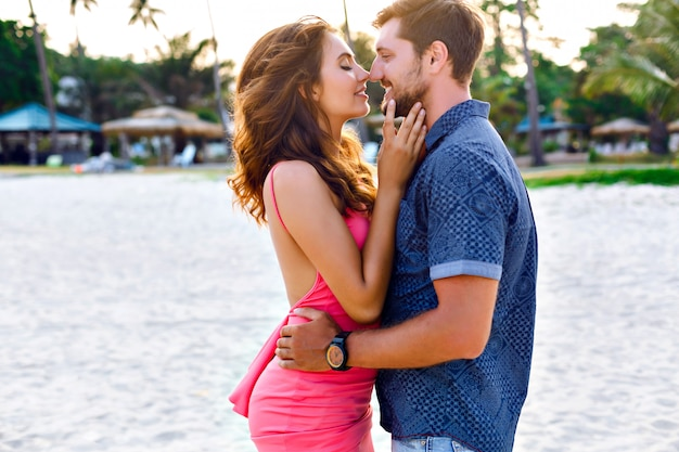 Happy sunny summer outdoor portrait of young stylish couple while kissing on the beach tropical island. wearing luxury fashion outfits, evening sunlight.