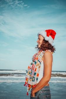 Счастливая молодая женщина загара в шляпе деды морозы и красочной повседневной одежде, идущей на пляже.