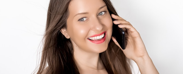 Счастливая загорелая женщина улыбается и звонит на смартфон на праздничный портрет на белой поверхности люди технологии и концепция коммуникации