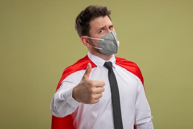 緑の背景の上に立っている親指を示すカメラを見て保護顔マスクと赤いマントで幸せなスーパーヒーローの実業家