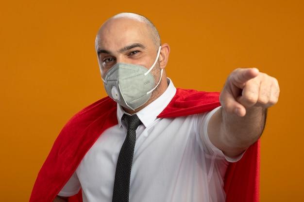 보호 얼굴 마스크와 오렌지 벽 위에 자신감 서 찾고 앞에 검지 손가락으로 가리키는 빨간 망토 행복 슈퍼 영웅 사업가