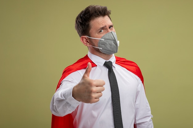 Happy super hero businessman in protective facial mask and red cape looking at camera showing thumbs upstanding over green background