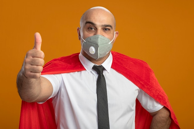 Happy super hero businessman in protective facial mask and red cape showing thumbs up