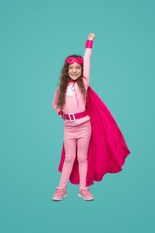拳を上げて幸せなスーパーヒーローの子供の女の子