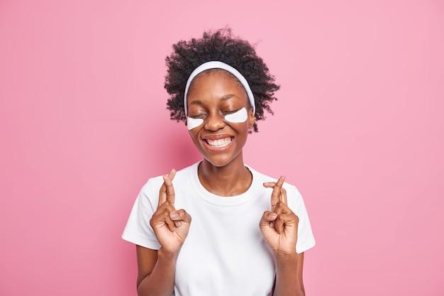 검은 피부 곱슬머리를 가진 행복한 미신적인 밀레니엄 여성은 손가락을 교차시켜 눈을 감고 피부 관리를 위해 패치를 적용합니다