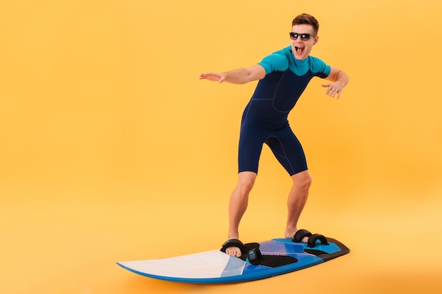 Happy surfer in wetsuit and sunglasses using surfboard like on wave