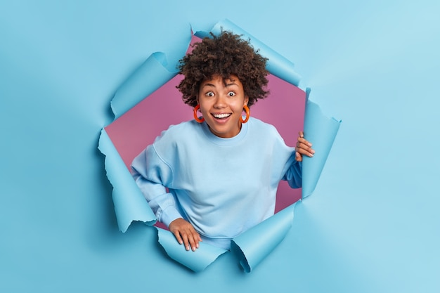 Happy surprised afro american teenage girl reacts on something awesome smiles broadly poses in torn paper blue wall dressed in casual jumper