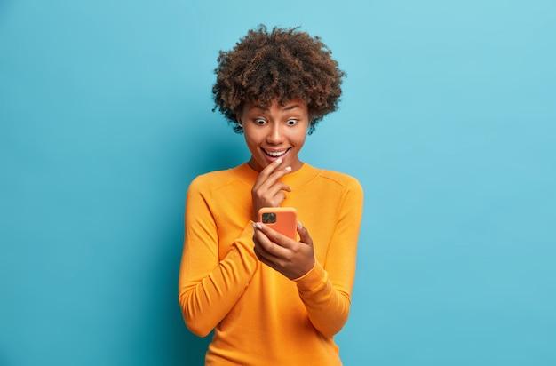 행복 놀란 아프리카 계 미국인 여자는 소셜 미디어 테스트에서 인터넷과 네트워킹을 탐색합니다. 스마트 폰을위한 새로운 응용 프로그램은 파란색 벽 위에 고립 된 캐주얼 점퍼를 착용합니다.