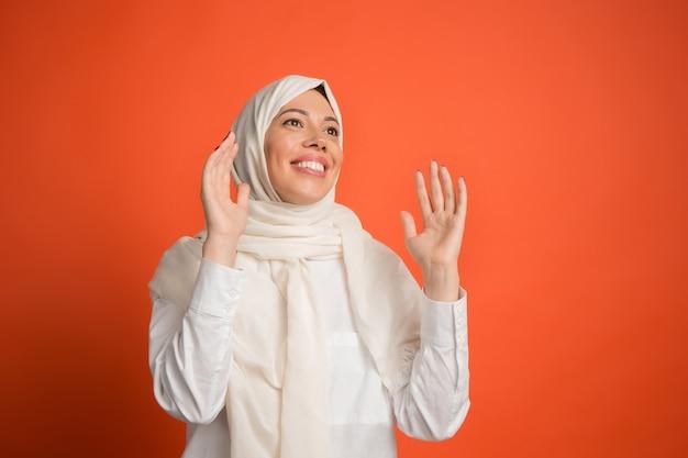 ヒジャーブで幸せな驚きのアラブの女性。赤いスタジオの背景でポーズをとって、笑顔の女の子の肖像画。若い感情的な女性。人間の感情、表情の概念。