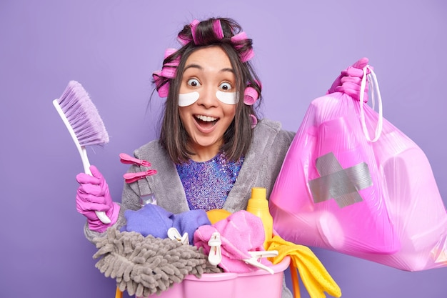 Happy surprised asian woman applies hair rollers for making hairstyle patches under eyes olds trash bag cleaning brush poses near laundry basket dressed in robe isolated over purple wall
