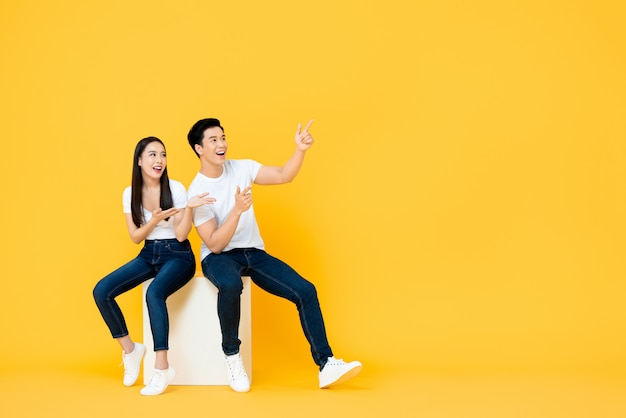 Happy surprised attractive young asian couple pointing and looking at blank space beside in yellow isolated stuidio wall
