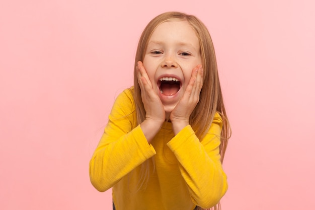 Счастливые удивленные эмоции ребенка. портрет очаровательной маленькой девочки, держащей руки на лице и кричащей от удивления, с широко открытым ртом и шокированным выражением лица. студийный снимок на розовом фоне