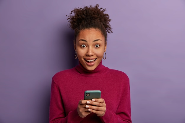 Happy surprised curly haired woman receives good news from friend, holds mobile phone, sends text mesages, wears casual turtleneck, isolated on purple wall, downloads app, browses internet