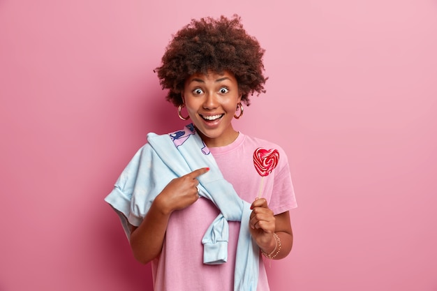 Happy surprised dark skinned woman indicates at herself, asks question, holds delicious lollipop, wears sweater tied over shoulder isolated on pink wall. teenager poses with sweet candy