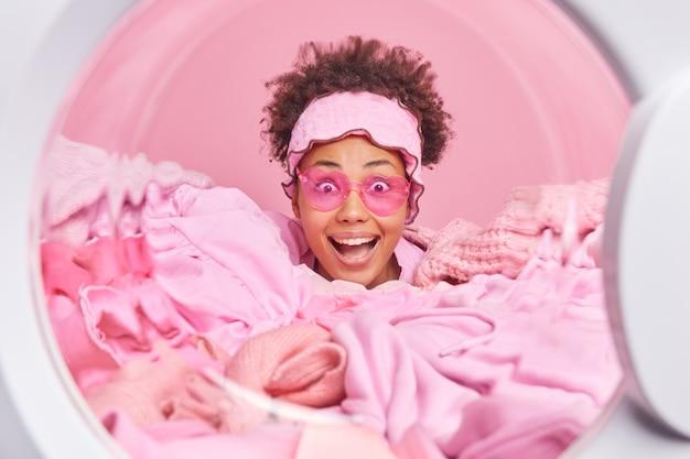 La governante femminile sorpresa felice con hiar riccio indossa occhiali da sole a forma di cuore rosa infila la testa attraverso la pila di bucato